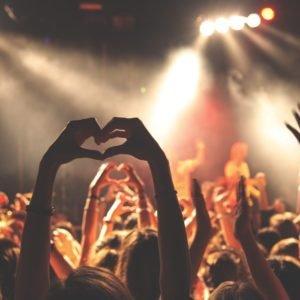 Garota formando um coração com a mão num show